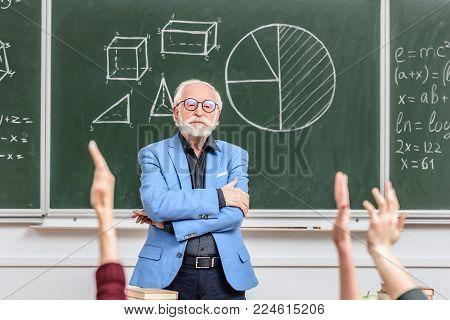 grey hair professor looking at students rising hands