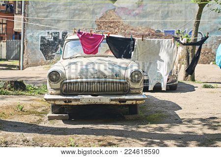 Old vintage car for parts in a Soviet style backyard where laundry is dried on a rope casting shadows