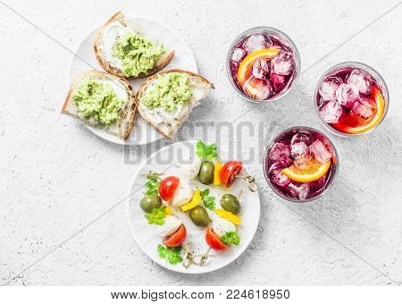 Aperitiv table - select and snack on a light background, top view. Sandwiches with avocado, canapes with mozzarella, tomatoes, olives and aperol spritz