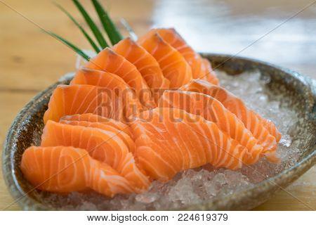 Raw salmon slice or salmon sashimi in Japanese style fresh serve on ice in bowl at Japanese restaurent.