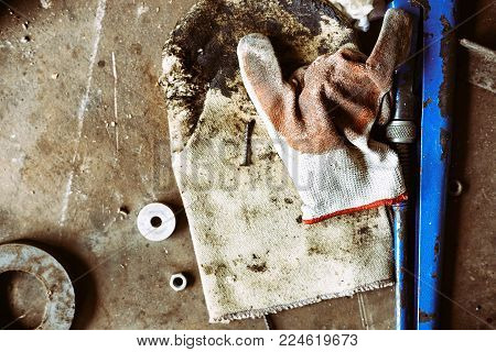 uncleared workshop with tools. on the dirty stone floor scattered tools