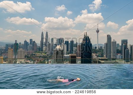 Kuala lumpur skyling in Malaysia. Young Asian girl enjoy swimming in swimming pool on roof top with beautiful city view Kuala lumpur, Malaysia.