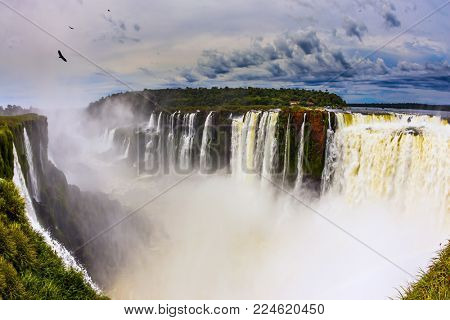Grandiose waterfalls Iguazu in the rainy season - the Devil's throat. Andean condors fly above the roaring Iguazu waterfall. Concept of active and photographic tourism