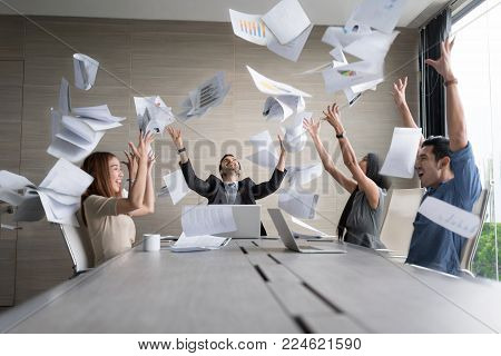 Teamwork business people excited happy and smile, throw papers and documents fly in air. Success team concept after sign contract.In selective focus and motion blur moving with perspective view.