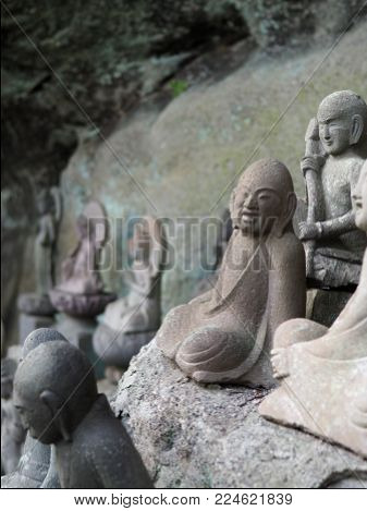 Ancient Buddhist arhat stone statue found in a small cave alcove on Mt. Nokogiri. Has a wonderful joyful expression on his face while seated in a yoga meditation position.