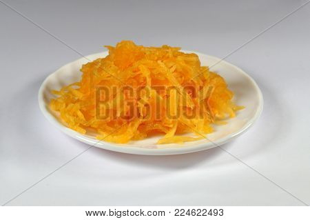 Pumpkin is grated with grater on a chopping board lined with a white plate