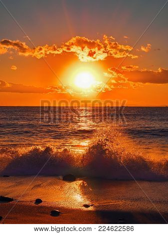 Surf and sunset at the beach. A wave breaks over as the sun comes down. Dynamic wave break amongst a breathtaking range of colors during a sunset in the land of the rising sun, Japan.