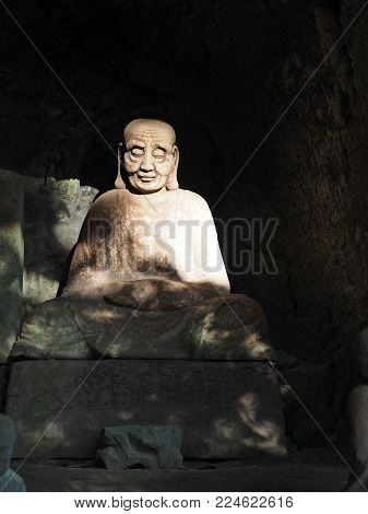 Ancient Buddhist arhat stone statue found in a small cave alcove on Mt. Nokogiri.