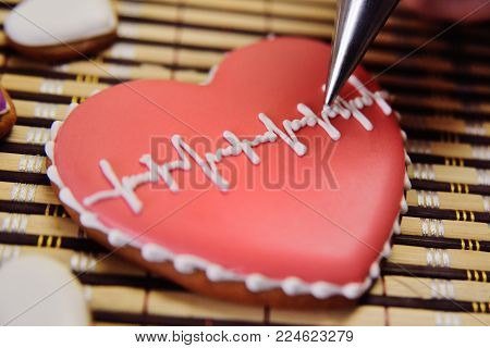 a female pastry cooks a glaze with a cardiogram on a gingerbread in the form of a heart. St. Valentine's Day, valentine's day, tradition, symbol