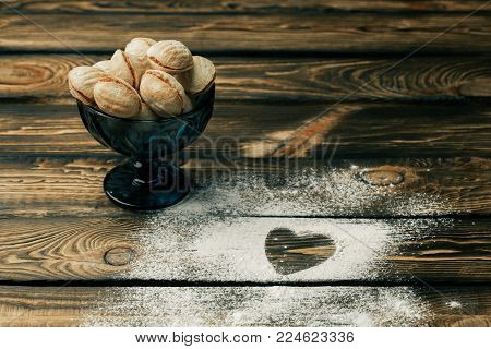 top view of heart shape wheat flour with the letter love. baking nuts over wooden background