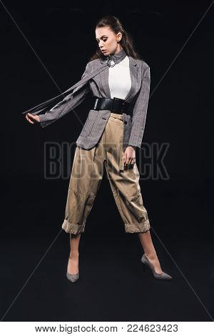 full length view of stylish young woman posing isolated on black
