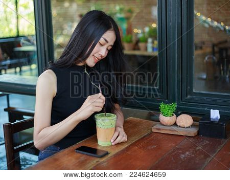 Woman Dinking Ice Green Tea Latte In The Cafe