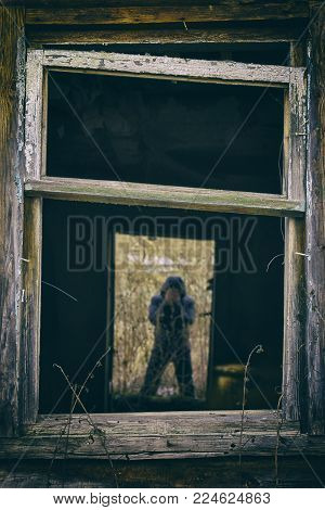 Dark silhouette of a man covering his face with hands in the doorway of abandoned house. View through the broken window.