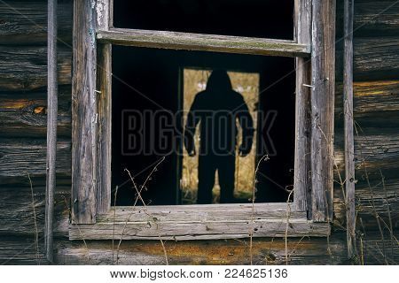 Dark male silhouette standing in the doorway of abandoned house. View through the broken window.
