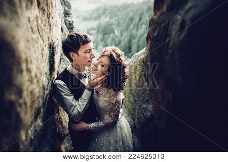 Young and romantic bride with her loving groom posing in darkened sandstone cleft