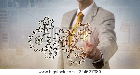 Unrecognizable businessman is touching a hand drawn gear train forming a model for successful operations. Concept for project management, corporate strategy, business success, team work and progress.