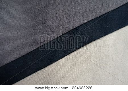 Diagonal black stripe sewn to grey and beige fabric
