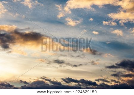 beautiful cloudy sky at sunset. abstract cloud formations colored in to gold by sunlight from below. lovely nature background