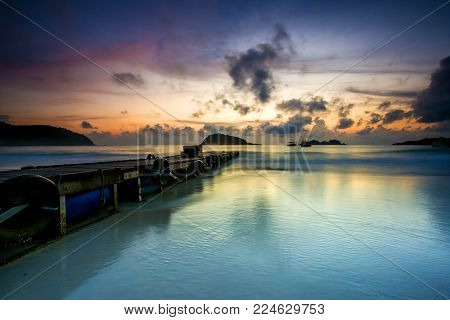 scenery of sunrise at redang island jetty.soft focus,motion blur due to long exposure. visible noise due to high iso