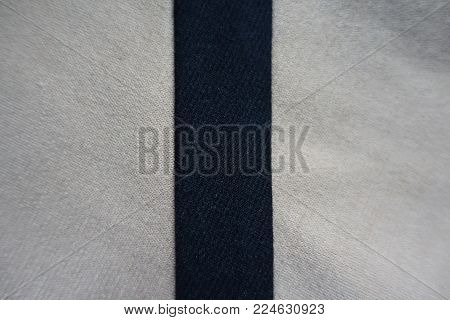 Narrow black ribbon sewn to beige fabric vertically