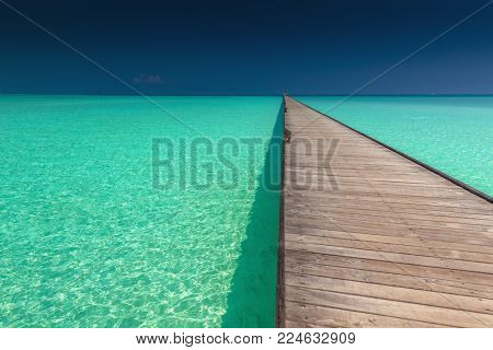 Wooden long jetty over lagoon with amazing clean azure water, Maldives