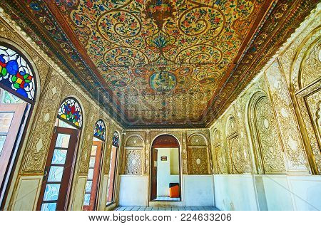 SHIRAZ, IRAN - OCTOBER 12, 2017: Preserved interior of Zinat Ol-Molk mansion with wooden ceiling, decorated with floral patterns and walls with reliefs of carved plaster, on October 12 in Shiraz.