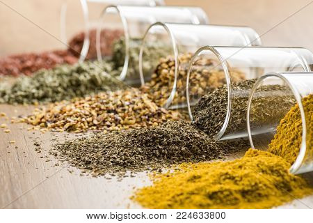 glass jars with various spices on wooden table, closeup on oregano.