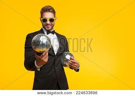 Content man in elegant classy suit and sunglasses holding shining disco balls posing on orange.