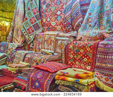 The Persian knotted-pile carpets and nomadic tribal woven rugs attract people with bright colors, complex patterns and high quality, Vakil Bazaar, Shiraz, Iran.