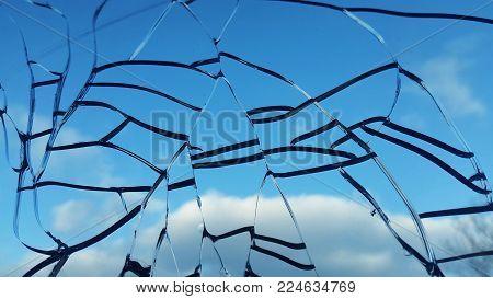 broken window with mesh cracks overlooking the sky and clouds.