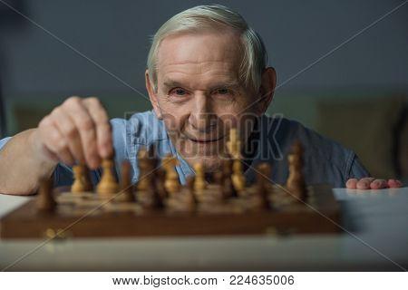 Senior smiling man playing chess board game