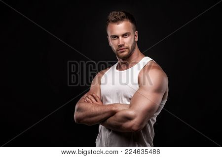 Studio portrait of athletic young man with arms crossed wearing white undershirt isolated on black background