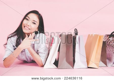 Asian smiling woman so happy with her shopping in casual clothing with shopping bags on the wall pink background, Vintage tone.  Lifestyle Concept.