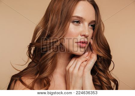 Close up Beauty portrait of pretty ginger woman with long hair looking away while posing with arms near face over cream background