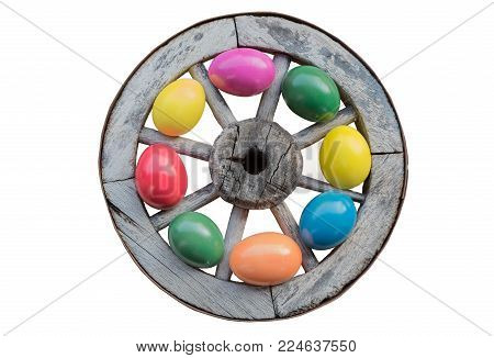 easter decoration - old wooden wheel with colorful tinted easter eggs, isolated on white background