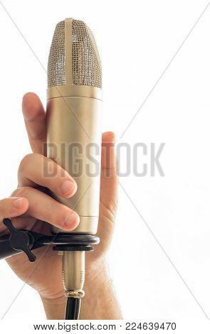 A microphone is on a mic stand.  A hand man's hand is  holding onto the microphone. The background is all white.