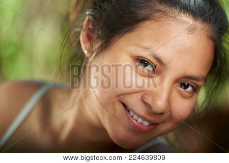 Headshot of smiling latino girl with natural makeup