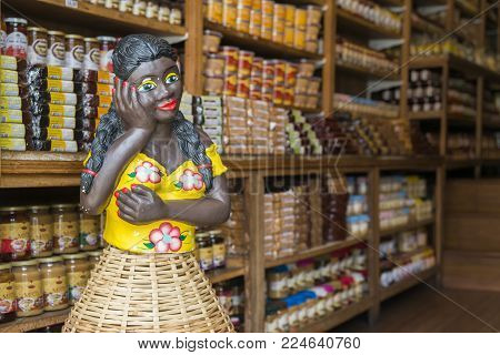 Ouro Preto, Brazil - Dec 28, 2017: Afrobrazililian woman mannequin in a food shop with local products in Ouro Preto, Minas Gerais, Brazil