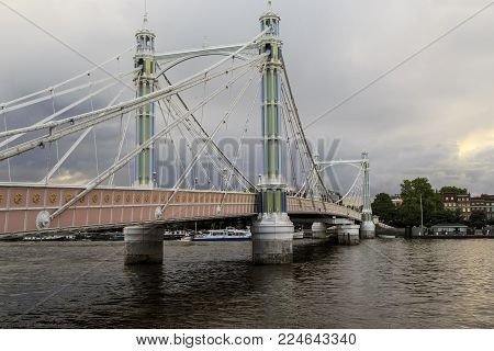 LONDON, GREAT BRITAIN - MAY 22, 2014: This is the Albert Bridge across the River Thames on a cloudy spring evening.