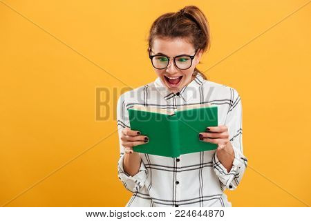 Photo of cheerful woman involved in reading fascinating book holding in hands isolated over yellow background