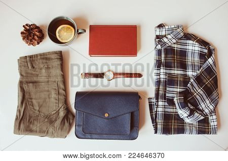 hipster or traveller woman casual fashion set flat lay. Plaid shirt, blue cross body bag  and khaki pants on white background with cup of tea. Stylish outfit top view.