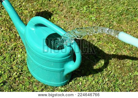 The water hose flows from the garden hose into the watering can.