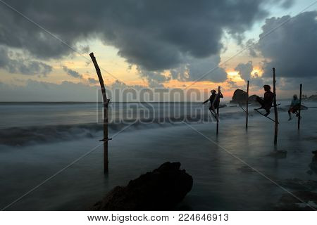 The stilt fishermen in the sunset at Koggala in Sri Lanka