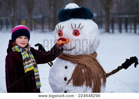 A small cheerful girl holds a big carrot, the nose of a big snowman. A cute little girl has fun in winter park, wintertime