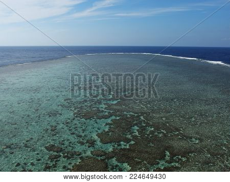 Coral reef in bird's eye view. The waves delimit an underwater coral cliff.