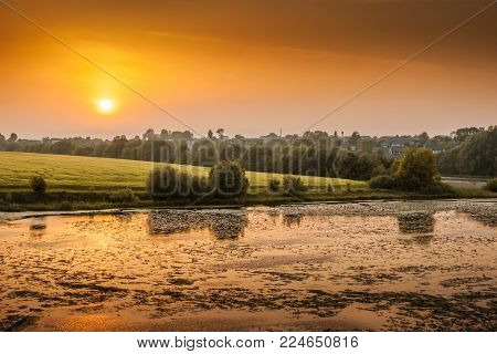 evening landscape, the sun is low above the horizon, the sky and trees reflect in the river