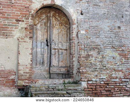 Old wooden door in old brick wall