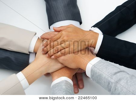 Image of business people hands on top of each other symbolizing partnership