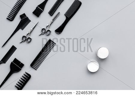Beauty saloon equipment. Hairdress and haircut. Combs, sciccors, brushes on grey background top view.