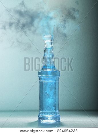 Blue magic potion releasing smoke and fume from a bottle